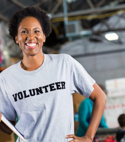 Pretty mid adult African American female food and clothing drive volunteer is standing in warehouse. She is holding a clipboard containing the warehouse's inventory. Shelves filled with donated items is in the background.